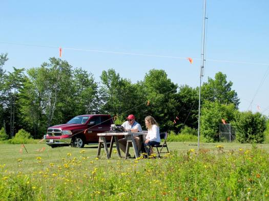 PARC President, Debbie Kaczowski (KB1WRY) mentors Ed Tatro (KC1FLG) out in the open on a beautiful Sunday afternoon at the Get-On-The-Air (GOTA) station. They are operating a KX3, KXPA100 to multi-band ground plane on 20 meter SSB. In the background, George Dean (WA1JMM) is operating 40 meter CW from his air-conditioned truck... Photo Credit: KB1WEA